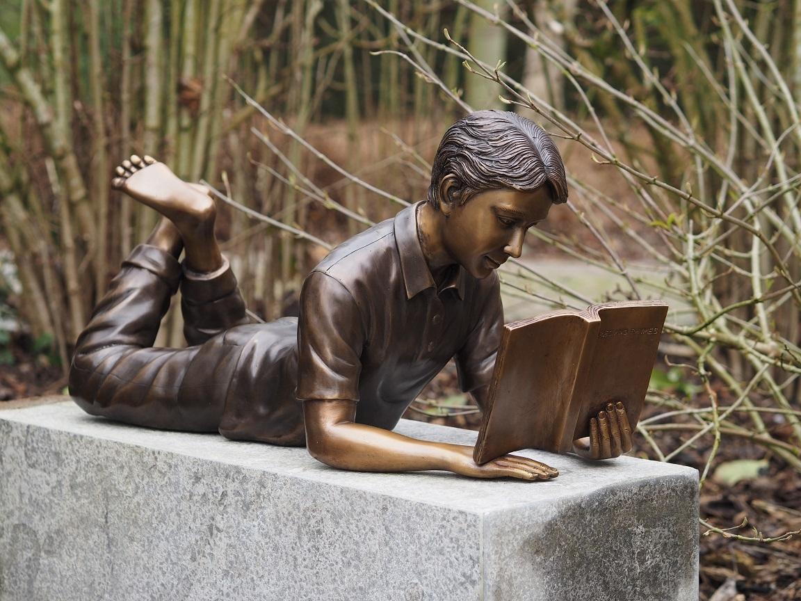 bronzen beeld - liggende lezende jongen