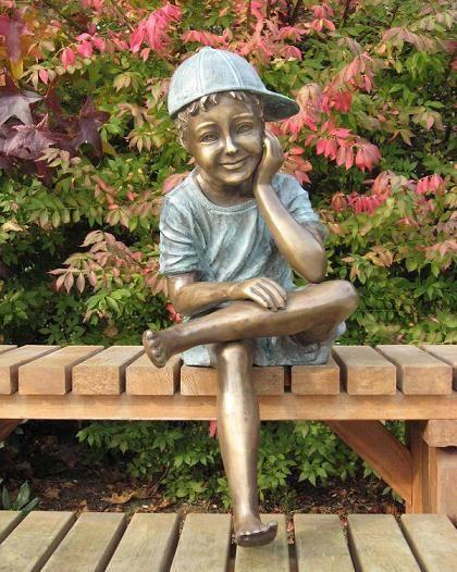 bronzen beeld - zittende jongen met pet